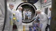 Кадър предоставен от Национално управление по въздухоплаване и изследване на космическото пространство, НАСА, представящ инженери, зареждащи товар в космическия кораб на ракетата Northrop Grumman Antares.