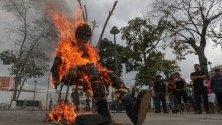 Последователи на правителството на Никола Мадуро горят кукла, представляваща образа на президента на САЩ- Доналд Тръмп, като форма на протест и част от честванията за Страсната седмица във Венецуела.