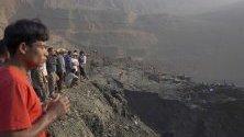 Хората се събират близо до мястото на свлачище в минна нефтена мина в Хпакант, щат Качин, Северна Мианмар, 23 април 2019 г. Според данните се смята, че над 50 миньори са погребани под купчина земя, изместена от свлачището.