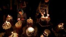 Православни вярващи палят свещи в очакване на благословията на великденските сладкиши, на православна църква по време на Великденска служба в Бишкек, Киргизстан.