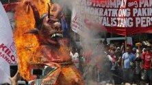 Протестиращите изгоряват фигура, която се подиграва с филипинския президент Родриго Дюртър, по повод отбелязването на Деня на труда в Манила, Филипини.