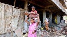 Индийка носи детето си на главата си близо до строителна площадка по повод Международния ден на труда или майския ден в Бхопал, Индия.