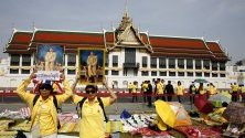 Тайландци държат портрети на крал Маха Ваджиралонгкорн Бодиндрадебаяварунгкун, докато чакат да го почетат по време на церемонията по кралската коронация на балкон на Судайсаваря Прасад Хол, пред Големия дворец в Банкок, Тайланд.