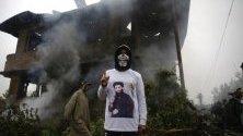 Кашмирска младеж, облечена в риза, изобразяваща военния командир Закир Муса, пред повредената къща, където Муса е бил убит в село Дадсара в Трал, южно от Шринагар, лятната столица на индийския Кашмир, Индия.
