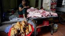 Жена продава свинско месо на пазарен щанд в Ханой, Виетнам. Виетнам е убил над 1,7 милиона прасета, или приблизително 5 процента от популацията на свине в страната.