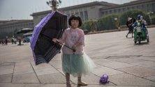 """Китайско момиче стои с чадър на площад Тянанмън в Пекин, Китай. Тази година се отбелязва 30-ата годишнина от протестите на площад """"Тянанмън"""" през 1989 година. Между 15 април и 04 юни 1989 г. студенти, интелектуалци и активисти участваха в поредица от демонстрации срещу китайската комунистическа партия, където последващите репресии от страна на властите предизвикаха голям брой смъртни случаи и наранявания на цивилни."""