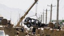 Войниците на НАТО преместват разрушено бронирано превозно средство от американски конвой след взрив. В Кабул избухна кола бомба, която уби и рани поне седем души.