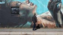 Човек минава покрай произведения на немския художник Норм Абартиг  и южноафриканския художник Николас Кер като част от проекта Westdene Graffiti в центъра на Йоханесбург, Южна Африка.