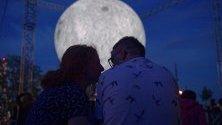 Хора гледат инсталация от британския художник Люк Джерам, представена в Научния център Коперник във Варшава, Полша. Инсталацията показва луна с диаметър седем метра. Всеки сантиметър на сферата е пет километра от повърхността на действителната луна.