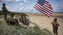 Френски ентусиасти, облечени като американски войници от Втората световна война, седят до американски флаг, засаден в пясъчна дюна на плажа Омаха на брега на Нормандия малко преди честването на 75-та годишнина на Деня на Д, който бележи началото на края на Втората световна война в Европа.
