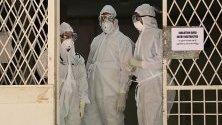 Медицински персонал пред на входа на изолираното отделение на Медицинския колеж в Кочи, Индия. Властите потвърдиха, че 23-годишен студент е заразен с вируса Нипах. Този вирус се разпространява чрез плодови прилепи и все още няма открита ваксина срещу вируса.