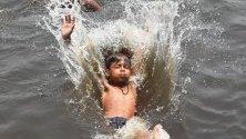 Индийско момче скача в канализационния канал на града, за да се охлади в Ню Делхи, Индия.