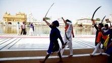 Членове на радикални сикхски организации крещят прохалистански лозунги и размахват мечове по време на мемориал за жертвите по време на операция Синя звезда през 1984 г., в Златния храм, най-святото място на сикхите в Амритсар, Индия.
