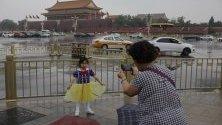 Китайско момиче позира за снимка на площад Тянанмън в Пекин, Китай.