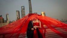 Китайска двойка позира за снимките си преди сватбата на Бунд пред кулата Шанхай в района на Пудонг, Шанхай, Китай.