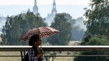 Жена използва чадър, за да се защити от слънцето, докато ходи в Дрезден, Германия.