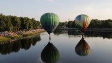 Балони с горещ въздух в полет над река Ловат по време на 24-та Международна среща с балони в Велики Луки, Русия.