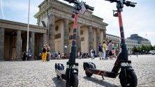 Електрически скутери, които се отдават под наем, стоят пред Бранденбургската врата в Берлин, Германия.