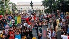 Скейтбордисти вдигат дъски по време на сбирка  за да отбележат Деня на скейтборда в Манила, Филипините.