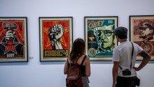 Посетители гледат творбите на американският уличен художник Шепард  Фейри (известен още като OBEY) по време на откриването на неговата изложба  Facing the Giant: Three Decades of Dissent в галерия Itinerrance Gallery в Париж, Франция.