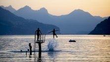 Младежи се радват на вечерта на езерото  Walensee в Швейцария.