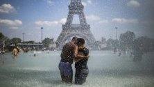 Двойка се охлажда във фонтаните на Трокадеро, срещу Айфеловата кула, по време на горещини в Париж, Франция.