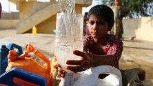 Местни жители изчакват да напълнят кутиите си с питейна вода в Карачи, Пакистан. Недостиг на вода засяга различни части на града от началото на лятото.