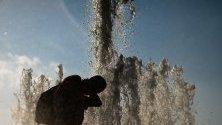 Човек се охлажда с вода във фонтан в парк Лустгартен в Берлин, Германия.