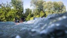 Човек  плува в река Ааре в горещ летен ден,  Берн, Швейцария.