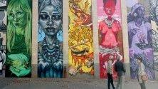 Туристите разглеждат огромни парчета графити на стената на сграда в центъра на Йоханесбург, Южна Африка.