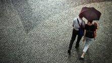 Двойка се разхожда с чадър по  мокри калдъръми в Мюнхен, Германия.