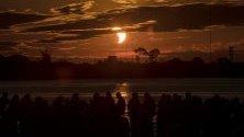 Хора наблюдават частичното слънчево затъмнение в Порто Алегре, Бразилия.