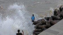 Индиец  позира за снимка по време на прилив в Арабско море на крайбрежната алея в Marine Drive в Момбай, Индия.