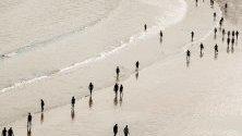 Хора се разхождат по брега на плажа Ла Конча, в Сан Себастиан, Испания.