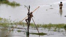 Индиец на риболов в наводнените земеделските полета в района на Асам, Индия.