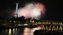 Фойерверки осветяват небето в близост до Айфеловата кула като част от празненствата на Деня на Бастилията в Париж, Франция.
