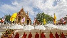"""Монаси рецитират молитви по време на церемония, известна като """"tak bat dok mai"""", в храма  Wat Ratchabophit в Банкок, Тайланд."""