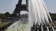 Хора се охлаждат във фонтаните на площад Трокадеро, срещу Айфеловата кула, в Париж, Франция.
