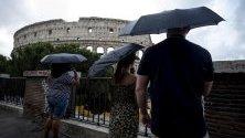 Туристи се опитват да се предпазят от дъжда с чадъри край Колизеумът в Рим, Италия.