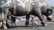 Мъж и дете карат колела под скулптура на крава на градската алея във Вентспилс, Латвия.