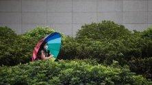 Жена се разхожда с чадър  в дъждовно време в Хонконг, Китай.