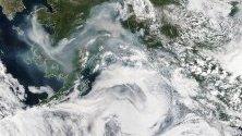 Снимка предоставена от НАСА на сателитно изображение, показващо гъст дим от огън, завихрящ се над щата Аляска, САЩ.