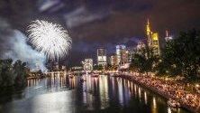 Хора се наслаждават на фойерверки осветяващи небето, след края на  фестивал във Франкфурт,Германия.
