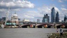 Хора се разхождат на брега на река Темза в Лондон, Великобритания.