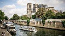 Туристическа лодка обикаля пред катедралата Нотр Дам в Париж, Франция.