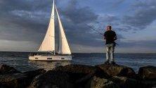 Рибар на брега на Балтийско море близо до Росток, Германия.