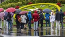 Туристи правят снимки на известния часовник с цветя под дъжда в Женева, Швейцария.
