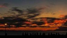 Хора се наслаждават на залеза на слънцето  над плажът  La Zuriola в Сан Себастиан, Испания.