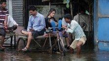 Индиец управлява рикшата си, пълна с пътници, по наводнените улици на село Раджпур, в Западен Бенгал, южно от Калкута. Повечето къщи в Раджпур се намират под вода.