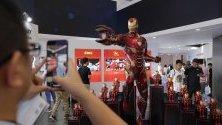 """Посетители разглеждат робота """"Железния човек"""" по време на на World Robot conference в Пекин, Китай. Там се представят над 700 нови робота."""
